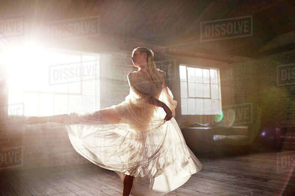 Graceful female dancer dancing in sunny studio Royalty-free stock photo