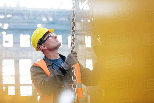 Steel worker holding chain in factory Royalty-free stock photo