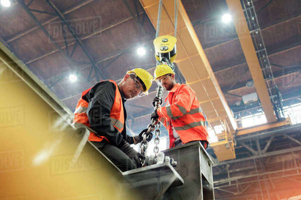 Steel workers fastening steel to crane in factory Royalty-free stock photo