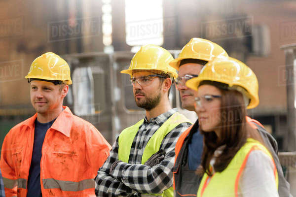 Steel workers listening in meeting in factory Royalty-free stock photo
