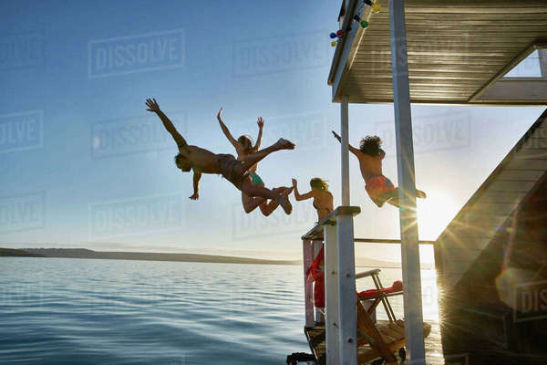 Young adult friends jumping from summer houseboat into sunny ocean Royalty-free stock photo