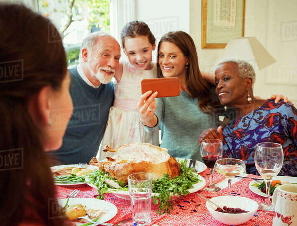 Multi-ethnic multi-generation family with camera phone taking selfie at Christmas dinner table Royalty-free stock photo