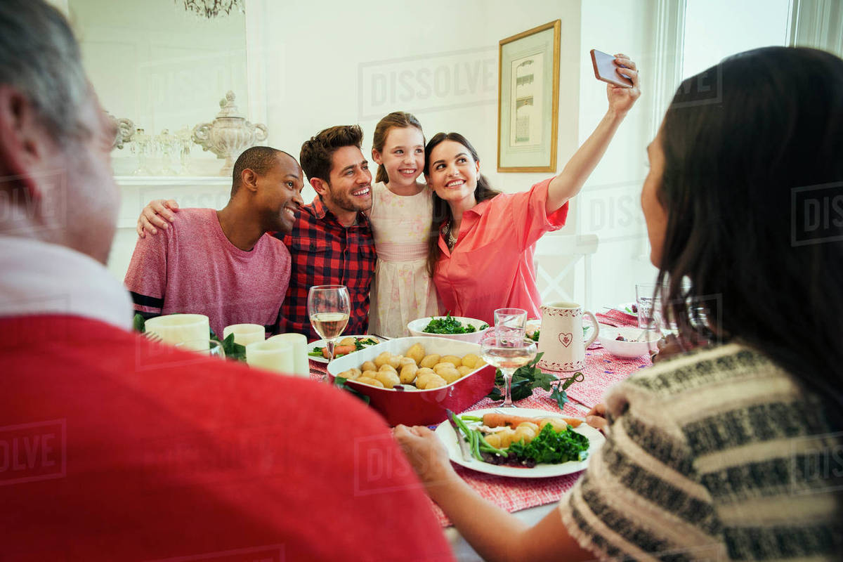 Multi Ethnic Family With Camera Phone Taking Selfie At Christmas Dinner  Table