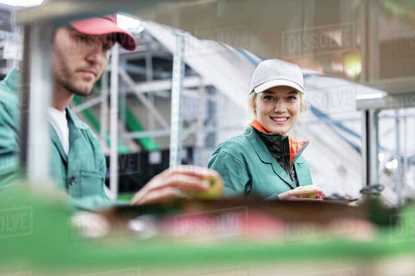 Portrait smiling female worker inspecting apples in food processing plant Royalty-free stock photo