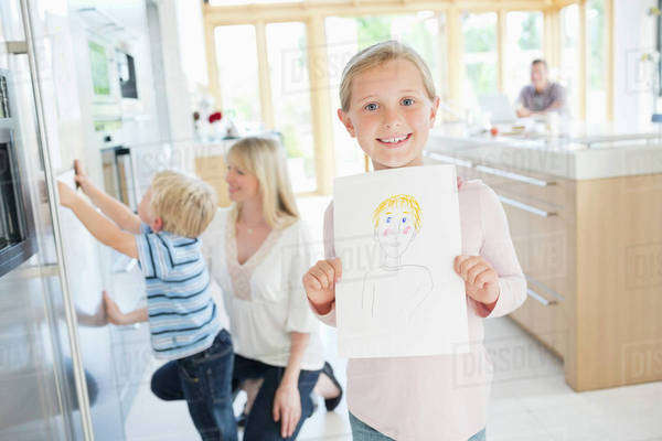 Girl showing off drawing in kitchen Royalty-free stock photo