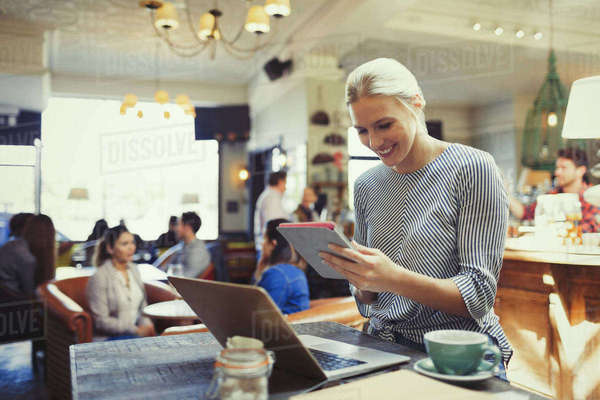 Smiling creative businesswoman using digital tablet and laptop in cafe Royalty-free stock photo