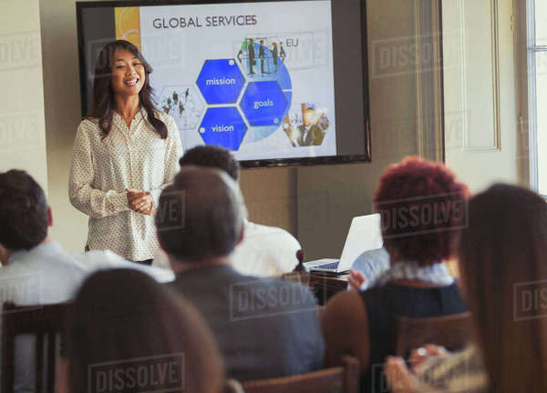 Smiling businesswoman leading business conference presentation at television screen Royalty-free stock photo