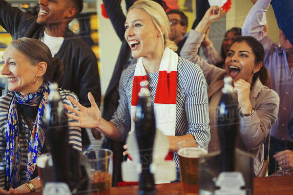Enthusiastic sports fans cheering and watching game at bar Royalty-free stock photo