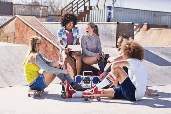 Friends in roller skates and on skateboard using digital tablet at sunny skate park Royalty-free stock photo