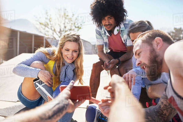 Personal perspective man showing friends video on smart phone at sunny skate park Royalty-free stock photo