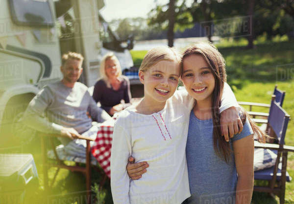 Portrait smiling sisters hugging outside sunny motor home Royalty-free stock photo