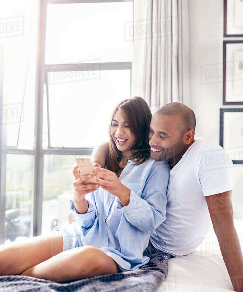 Smiling couple texting with cell phone on bed Royalty-free stock photo