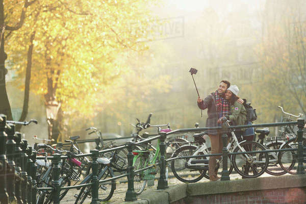 Young couple with bicycles taking selfie with selfie stick on autumn bridge, Amsterdam Royalty-free stock photo