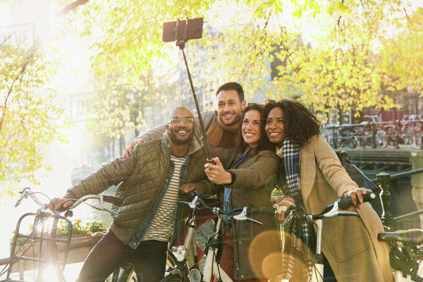 Smiling friends with bicycle taking selfie with selfie stick on urban bridge Royalty-free stock photo