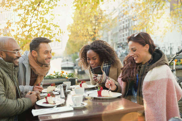 Friends eating cheesecake dessert at autumn sidewalk cafe Royalty-free stock photo