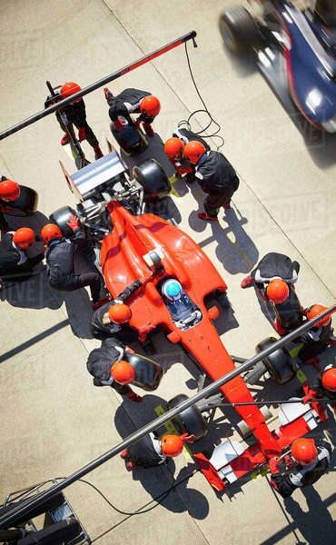 Overhead pit crew working on formula one race car in pit lane Royalty-free stock photo