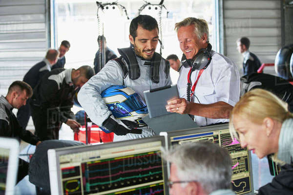 Manager and formula one driver with digital tablet talking in repair garage Royalty-free stock photo