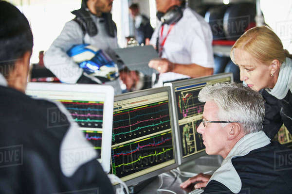 Formula one team reviewing diagnostics telemetry data on computers Royalty-free stock photo