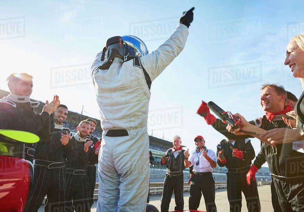 Formula one racing team and driver cheering, celebrating victory on sports track Royalty-free stock photo