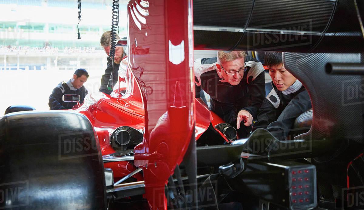 Pit crew mechanics examining race car in repair garage Royalty-free stock photo