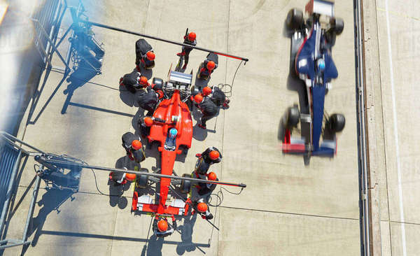 Overhead pit crew replacing tires on formula one race car in pit lane Royalty-free stock photo