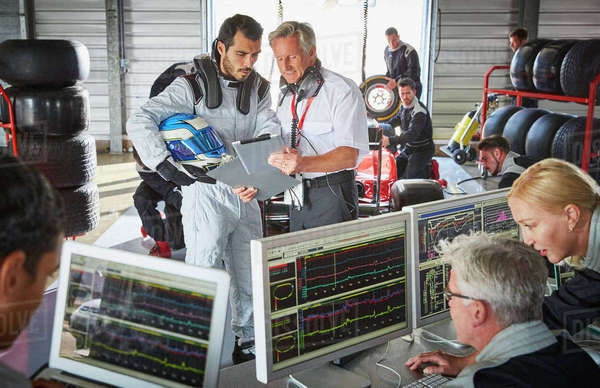 Manager and formula one driver discussing telemetry diagnostics in repair garage Royalty-free stock photo