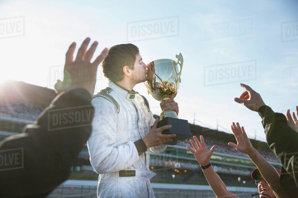 Formula one racing team cheering around driver kissing trophy, celebrating victory Royalty-free stock photo