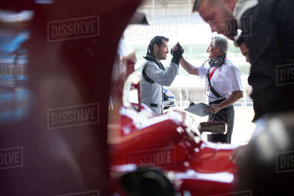 Manager and formula one race car driver high-fiving in repair garage Royalty-free stock photo