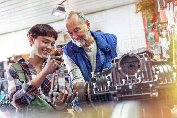 Male and female motorcycle mechanics repairing engine in workshop Royalty-free stock photo