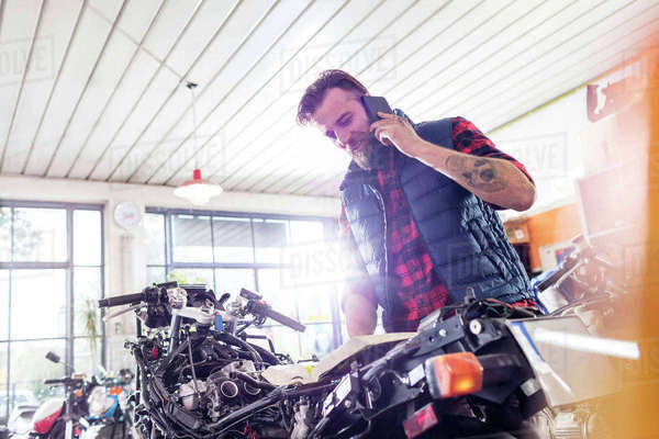 Motorcycle mechanic talking on cell phone in workshop Royalty-free stock photo