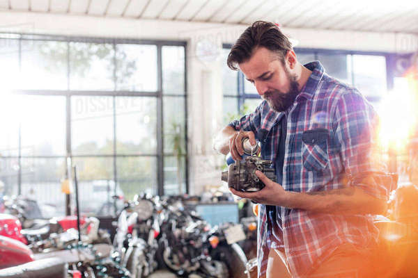 Motorcycle mechanic greasing engine part in workshop Royalty-free stock photo