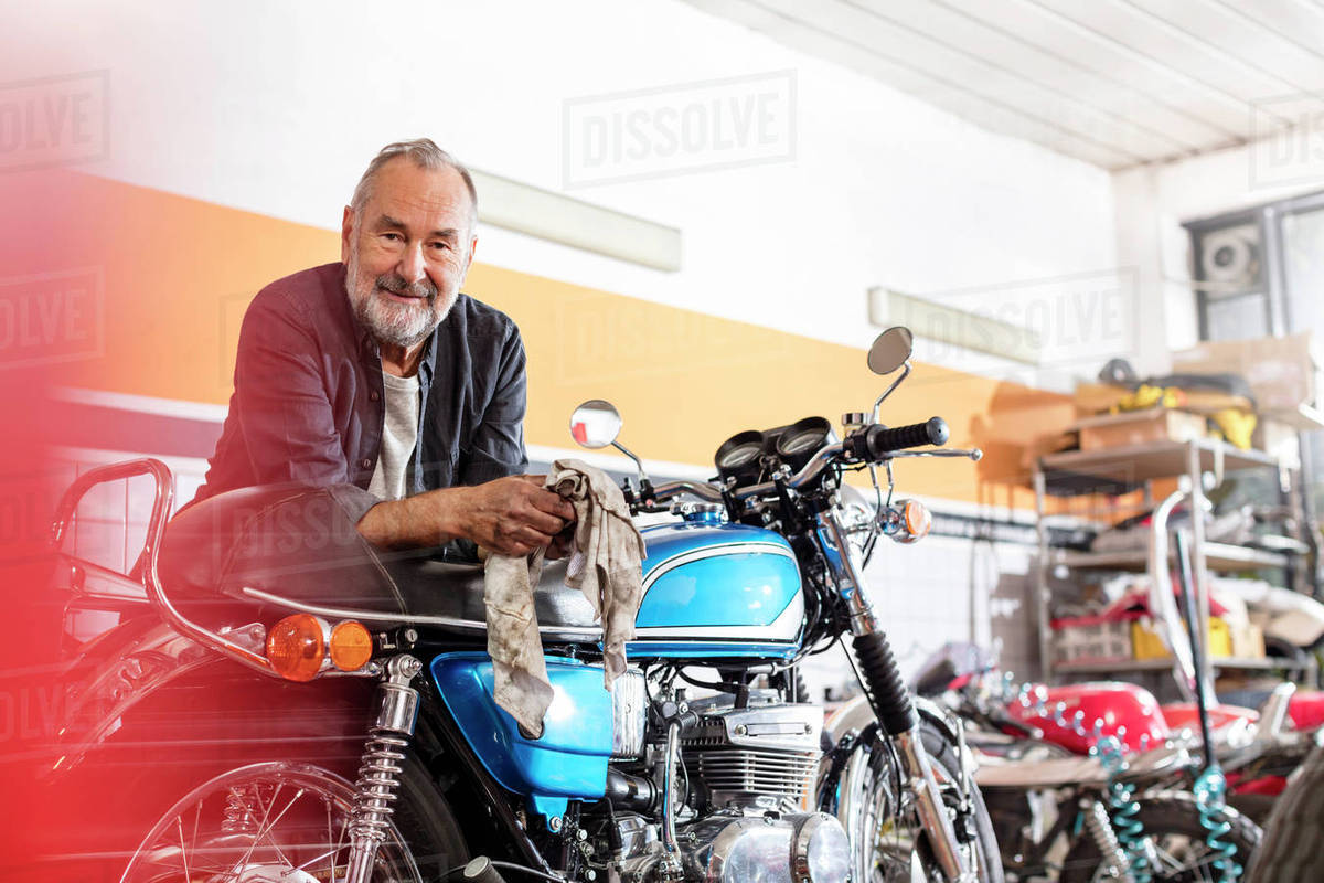 portrait confident senior male motorcycle mechanic leaning on motorcycle in workshop