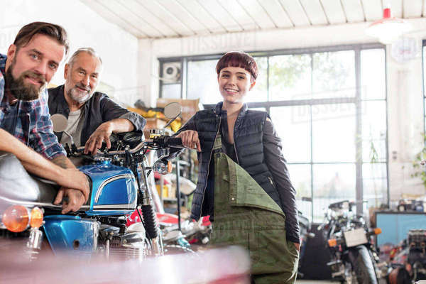 Portrait smiling male and female motorcycle mechanics in workshop Royalty-free stock photo