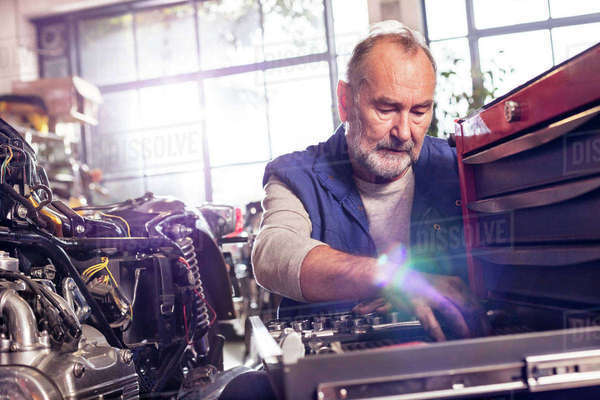 Senior male motorcycle mechanic retrieving tools in toolbox in workshop Royalty-free stock photo