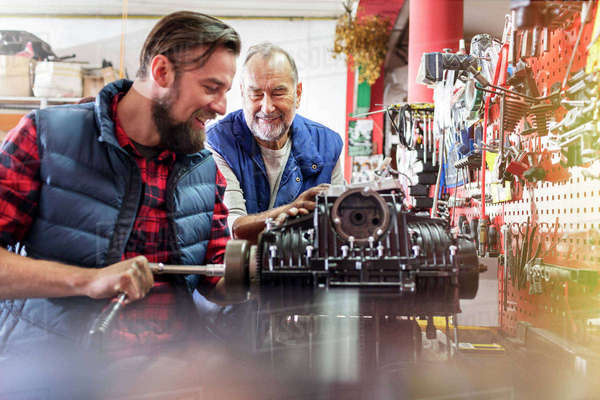 Male motorcycle mechanics repairing engine in workshop Royalty-free stock photo