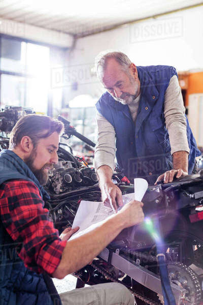 Male motorcycle mechanics reviewing plans in workshop Royalty-free stock photo
