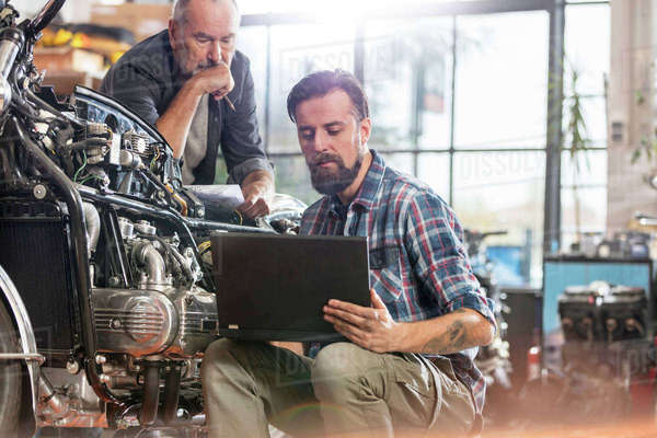 Male motorcycle mechanics using laptop in workshop Royalty-free stock photo