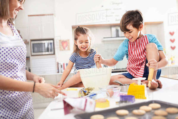 Mother and children baking cookies in kitchen Royalty-free stock photo
