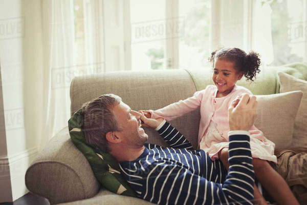 Affectionate multi-ethnic father and daughter holding hands on sofa Royalty-free stock photo