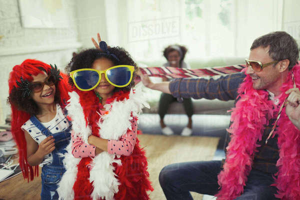 Portrait father and daughters playing dress up with oversized sunglasses and feather boas Royalty-free stock photo