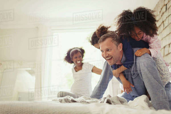 Multi-ethnic daughters tackling father on bed Royalty-free stock photo
