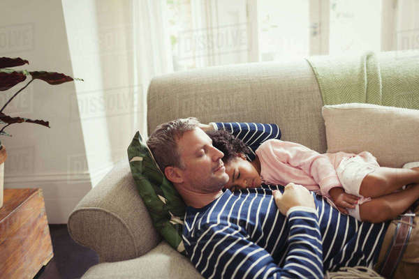 Affectionate, serene multi-ethnic father and daughter napping on sofa Royalty-free stock photo
