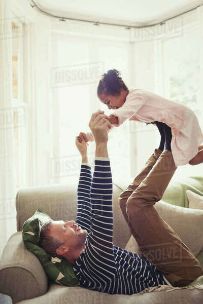 Multi-ethnic father playing, balancing daughter on legs overhead on sofa Royalty-free stock photo