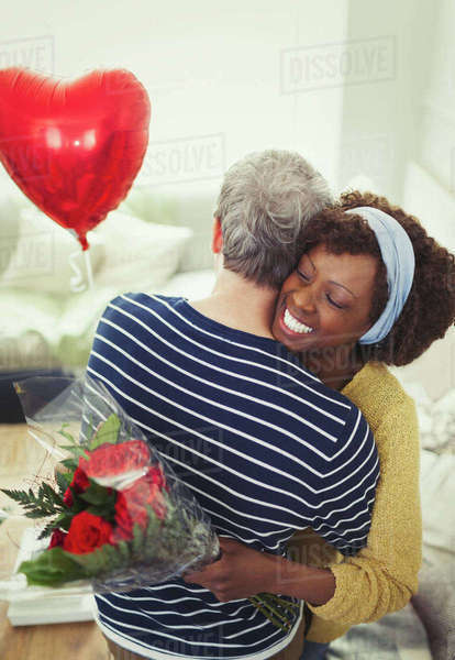 Wife receiving Valentine's Day rose bouquet and balloon, hugging husband Royalty-free stock photo