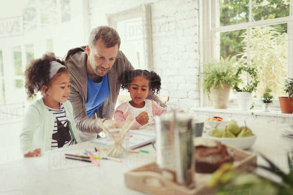 Multi-ethnic father and daughters coloring in kitchen Royalty-free stock photo