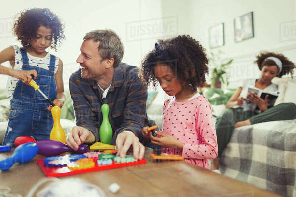 Multi-ethnic father and daughters playing with toys in living room Royalty-free stock photo