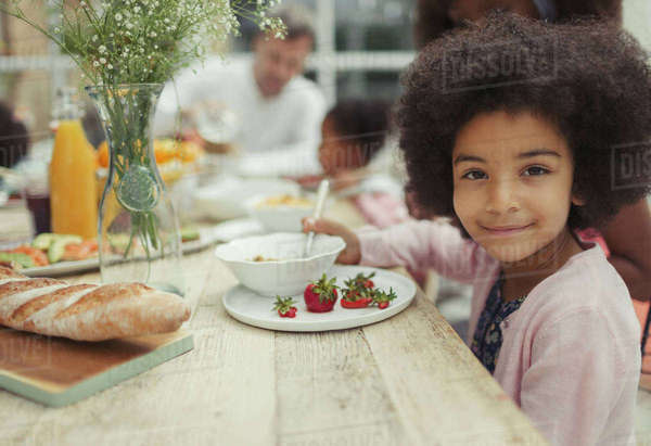 Portrait smiling girl eating strawberries at breakfast table Royalty-free stock photo