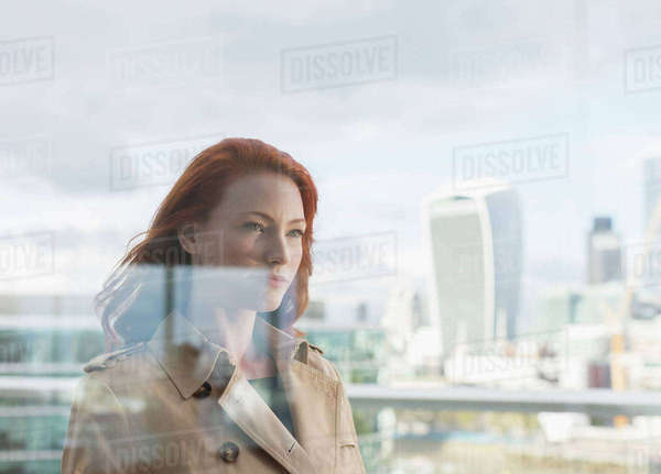Confident businesswoman with red hair on urban balcony with city view Royalty-free stock photo