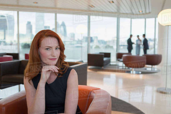 Portrait confident businesswoman with red hair in urban highrise office lounge Royalty-free stock photo