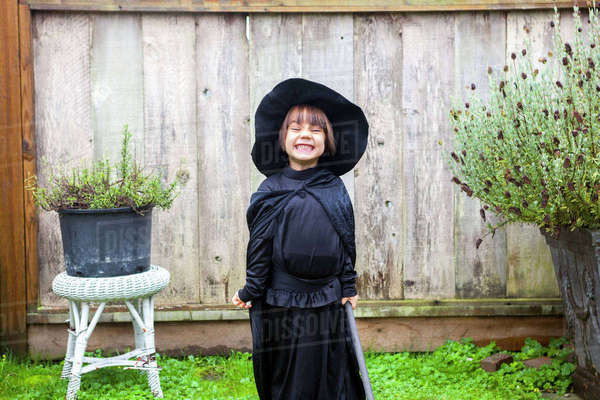 Portrait enthusiastic girl wearing witch costume in garden Royalty-free stock photo